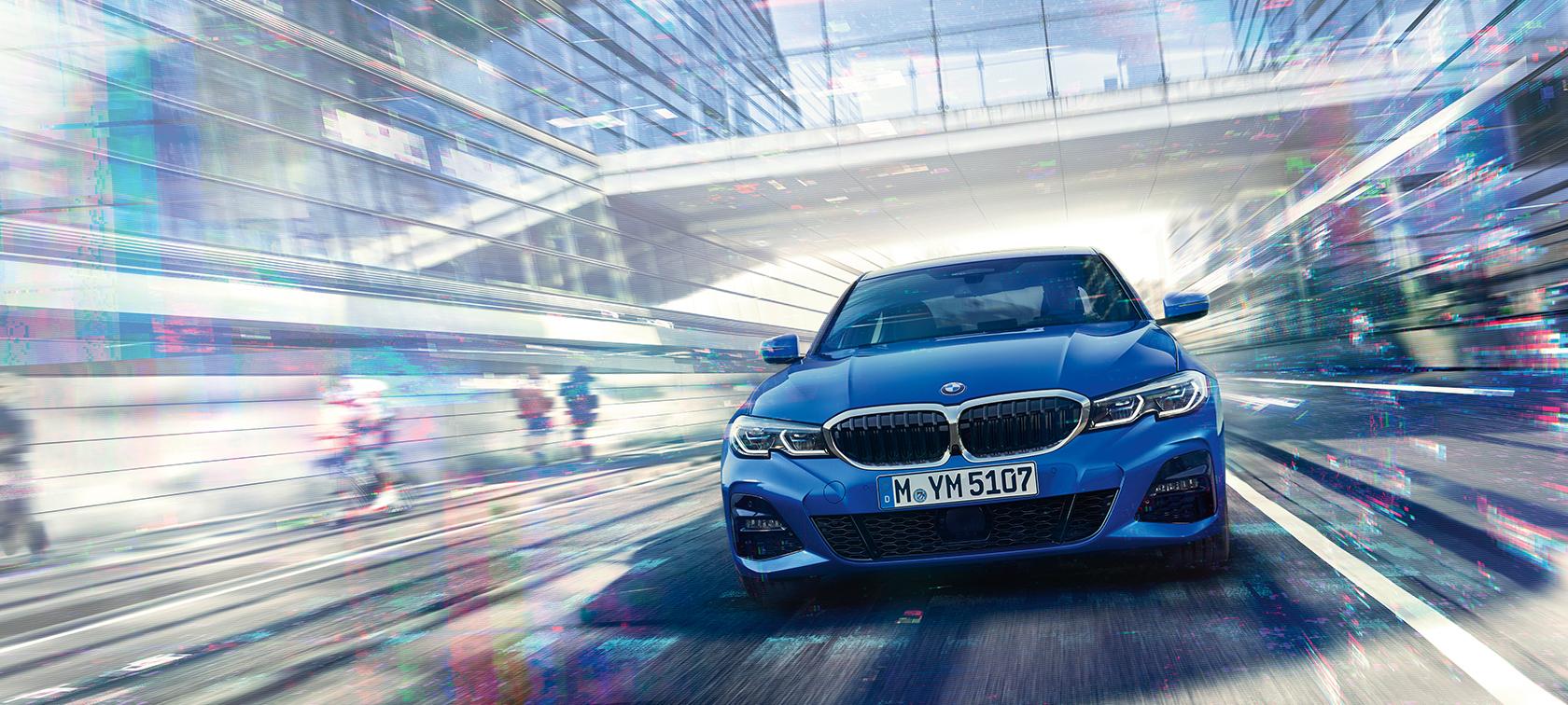 Egy üvegépület alatt suhanó BMW 3-as Limousine szemből.